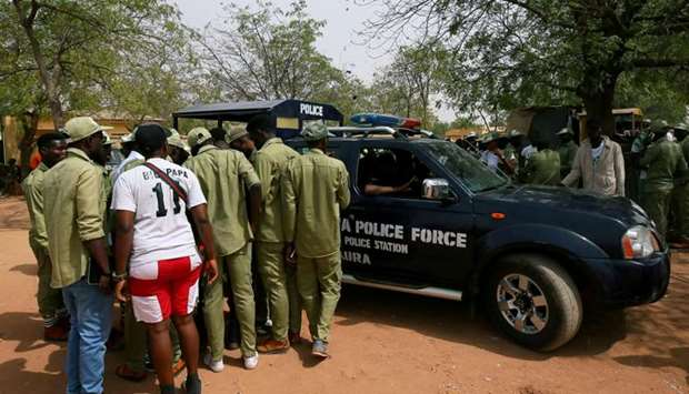 National Youth Service Corps members stand by a police car outside the Independent National Electora