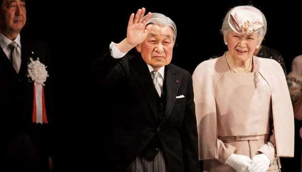 Japanese Emperor Akihito and Empress Michiko leave from a stage as Prime Minister Shinzo Abe looks o