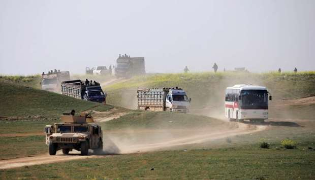 Trucks loaded with civilians ride near the village of Baghouz, Deir Al Zor province, Syria