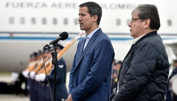 Juan Guaido (L) next to Colombian Foreign Minister Carlos Holmes Trujillo speaking upon arrival in B