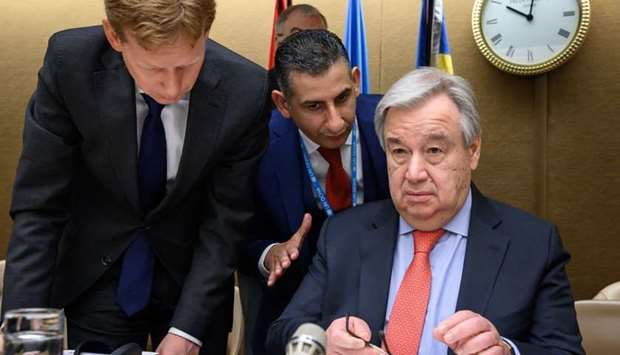 UN Secretary-General Antonio Guterres (R) looks on at the opening of a pledging conference for the h