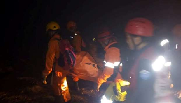Rescue workers carry a body bag containing a victim following the collapse of an illegal gold mine a