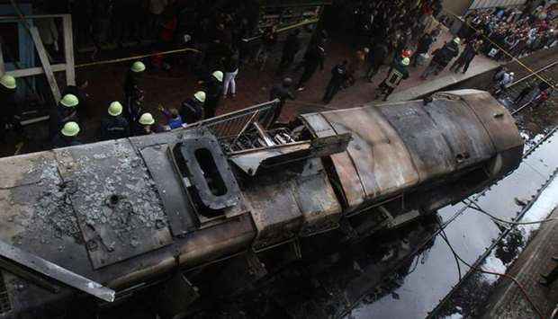 Fire fighters and onlookers gather at the scene of a fiery train crash at the Egyptian capital Cairo