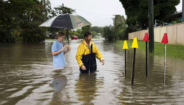 Local residents stand in floodwaters near Hermit Park, Townsville