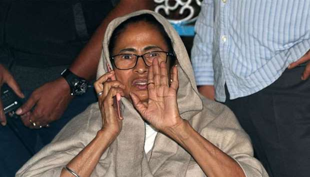 Mamata Banerjee speaks on her mobile phone as she sits in a protest against an attempted raid by Ind