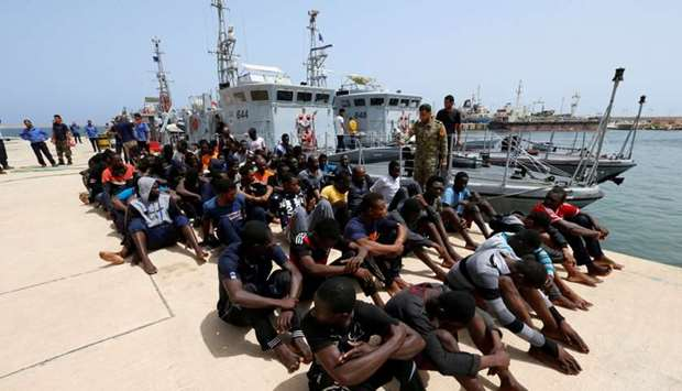 Migrants sit at a naval base after being rescued by Libyan coastguards in Tripoli, Libya