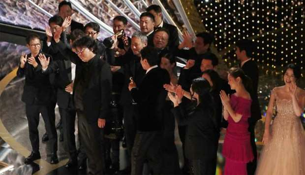 "Director Bong Joon Ho and the cast and crew of ""Parasite"" on stage after winning the Oscar for Best"