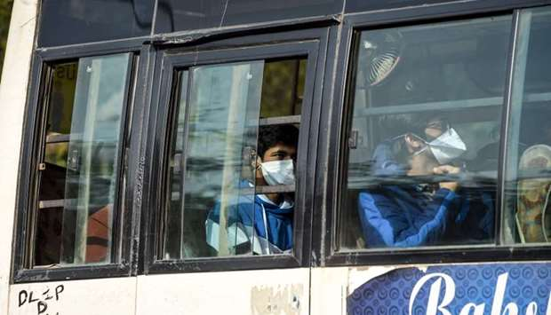 Indian nationals are transported in a bus out of the Indira Gandhi International Airport following t