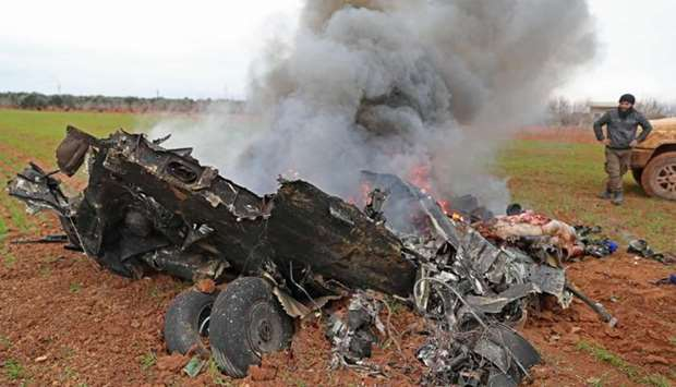 Syrian rebel fighters gather around the burning remains of a military helicopter after it was shot d