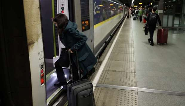 A woman enters a Eurostar train travelling from London to Paris, in London, Britain