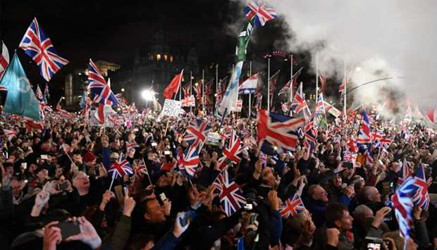 Brexit supporters wave Union flags as the time reaches 11 O'Clock, in Parliament Square, venue for t