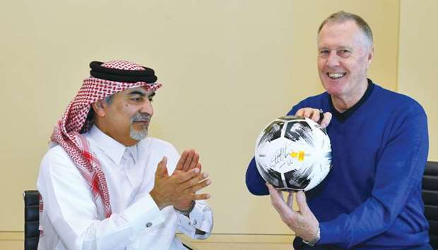 Sir Geoff Hurst holds a football after signing it on Wednesday in the presence of Qatar Olympic and