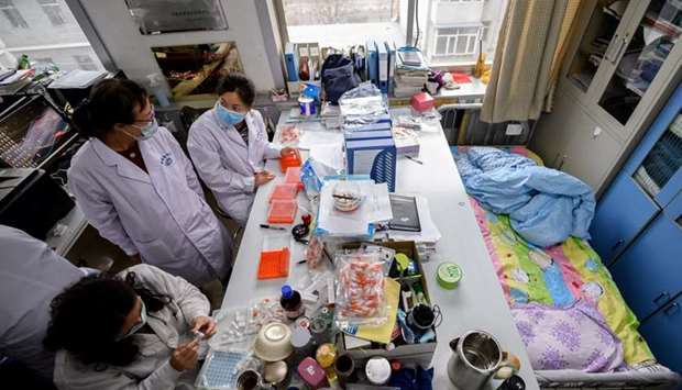 Workers are seen next to a bed placed inside an office at a centre for disease control and preventio