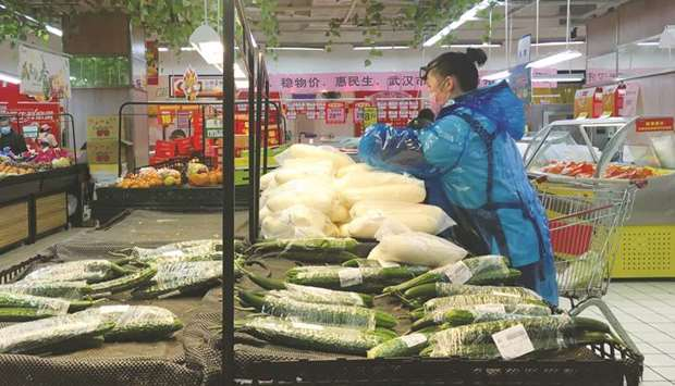 An employee sorts vegetables inside a supermarket in Wuhan, the epicentre of the novel coronavirus o
