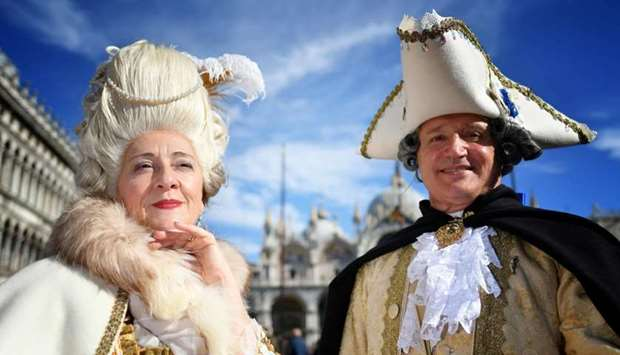 Revellers wearing a mask and a period costume take part in the Carnival