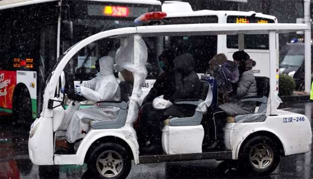 Worker in protective suit drives a vehicle amid snow to transport novel coronavirus patients outside