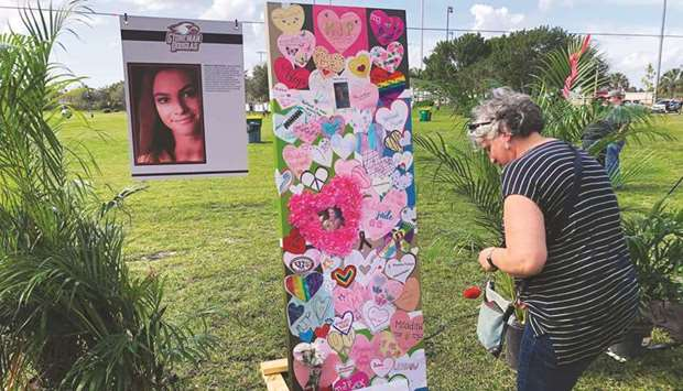 A woman leaves a tribute in front of the memorial of one of the 17 victims of Marjory Stoneman Dougl