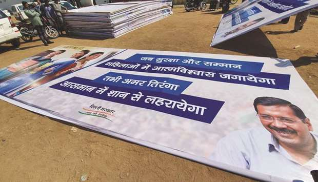 Workers prepare posters ahead of the swearing-in ceremony of AAP leader Arvind Kejriwal at Delhi's R