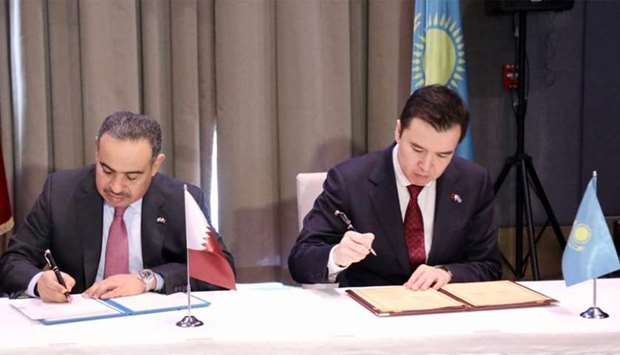 HE al-Kuwari and Dalenov co-sign the minutes of the meeting at the conclusion of fifth session of th