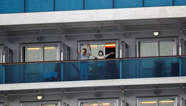 Passengers wave on the cruise ship Diamond Princess, as the vessel's passengers continue to be teste