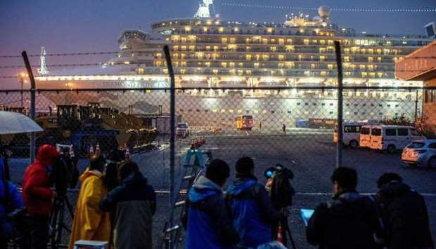 A bus arrives near the cruise ship Diamond Princess, where dozens of passengers were tested positive