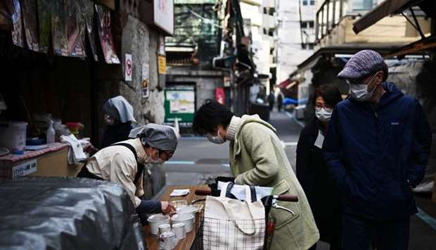A woman buys food in Tokyo's Tsukiji area. AFP