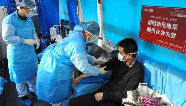 A man (R) who has recovered from the COVID-19 coronavirus infection donating plasma in Lianyungang i