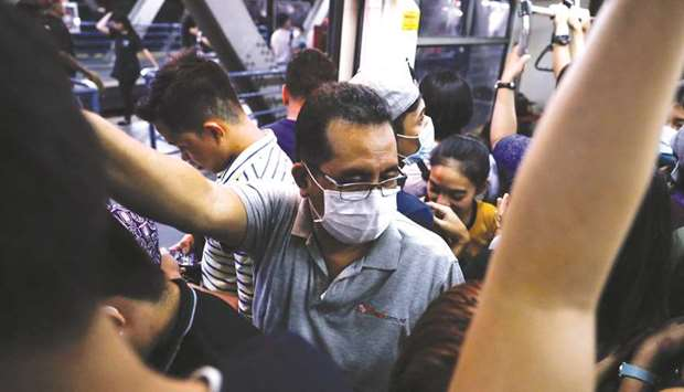 Passengers wear protective masks inside a crowded train in Manila, yesterday.