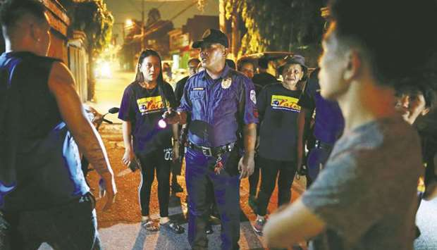 A policeman reprimands men for drinking in public, while accompanying a volunteer group of women pat
