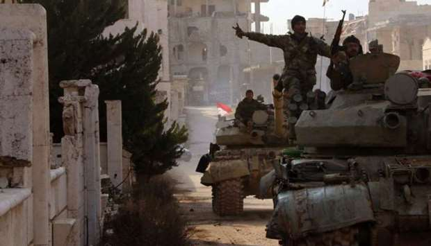 Syrian army soldiers gesture in town of Kafar Hamra, in Aleppo province, Syria