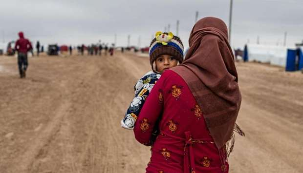 A Syrian woman carrying a child walks by, in the Washukanni Camp for the internally displaced, near
