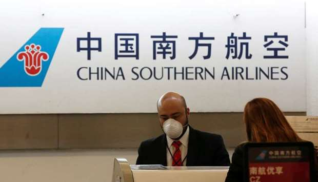 A China Southern Airlines employee wears a surgical mask as a preventive measure in light of the cor