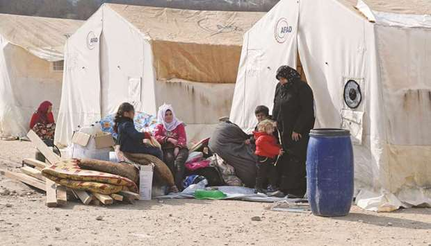Displaced Syrians sit outside their tents at Deir al-Ballut camp in Afrin's countryside, along near