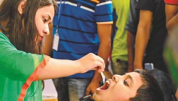 A child receives an oral cholera vaccine from a health worker during a vaccination campaign in Dhaka