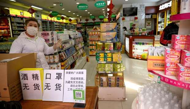 employees wearing protective face masks at a pharmacy in Beijing.