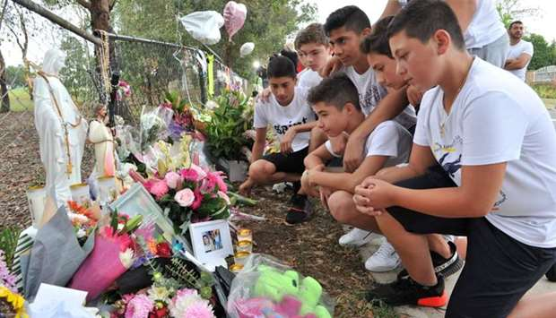 Schoolmates of one of the boys killed gather to pay their respects at a makeshift memorial at the si