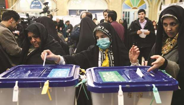 A woman wears a face mask as she casts her vote during parliamentary elections at a polling station