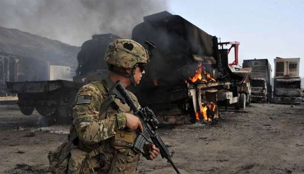 A US soldier investigates the scene of a suicide attack at the Afghan-Pakistan border crossing in To