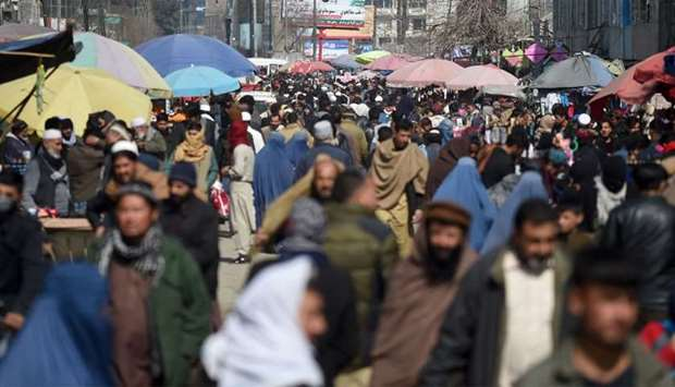 Pedestrians walk through a crowded market in Kabul