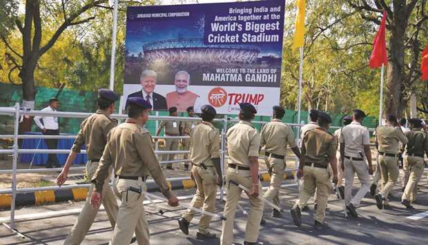 Police walk past a hoarding with the images of US President Donald Trump and Prime Minister Narendra