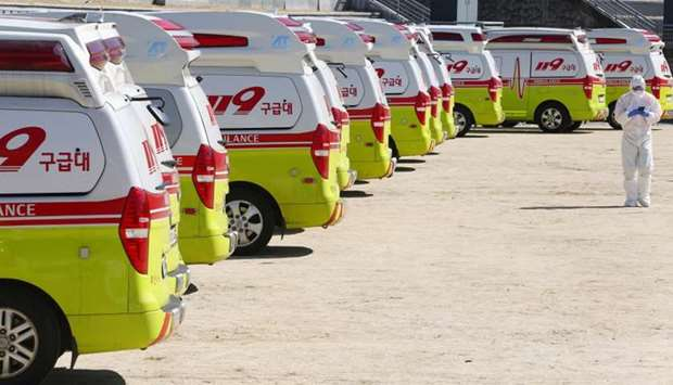 A medical worker gets ready as ambulances are parked to transport a confirmed coronavirus patient in