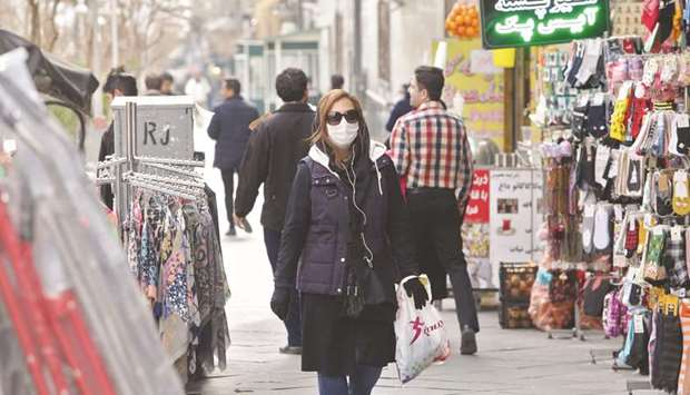A woman wears a protective mask while walking along the side of a street in the Iranian capital Tehr