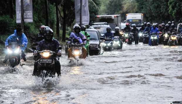 People ride motorcycles along a flooded street in Bekasi, near Jakarta, Indonesia