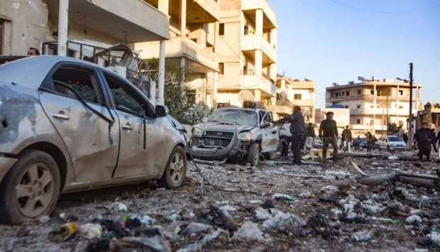 People check the damage in a street following an air strike by pro-Syrian regime forces in the town