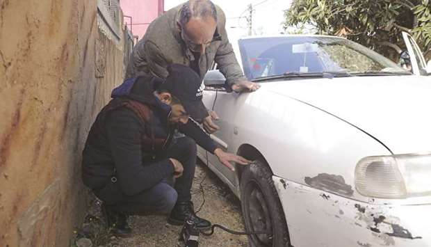 A man checks his slashed tyre in the occupied West Bank village of Yasuf near Nablus, yesterday.