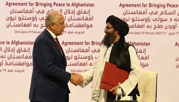 Khalilzad and Baradar shake hands after signing the agreement