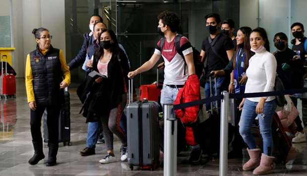 Mexican students wear protective masks upon their arrival at the Del Bajio International Airport, af