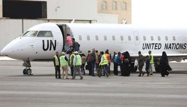 People board a United Nations plane which will carry them to Amman, Jordan in the first flight of a