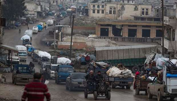 A convoy of trucks transporting Syrians and their belongings drives through the village of al-Mastum