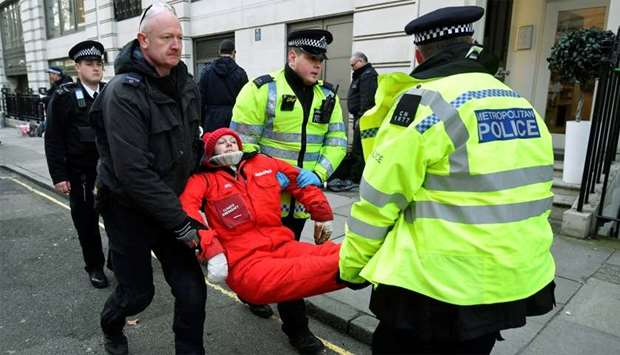Greenpeace climate activist looks on as she is being removed by police officers near the entrance to